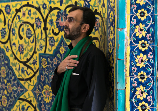 Shiite man praying in front of colorful faience tiles at Shrine of sultan Ali, Kashan County, Mashhad-e Ardahal, Iran