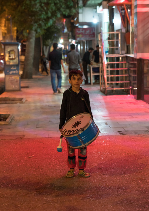 A child plays drums at night in the street during muharram, Lorestan province, Khorramabad, Iran