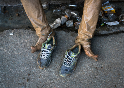 Iranian shiite muslim man legs and shoes after rubbing mud on his clothes during the Kharrah Mali ritual to mark the Ashura ceremony, Lorestan Province, Khorramabad, Iran