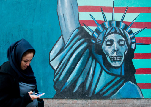 Woman with phone passing in front of an anti-american propoganda slogan depicting statue liberty skeleton on the wall of the united states embassy, Central district, Tehran, Iran