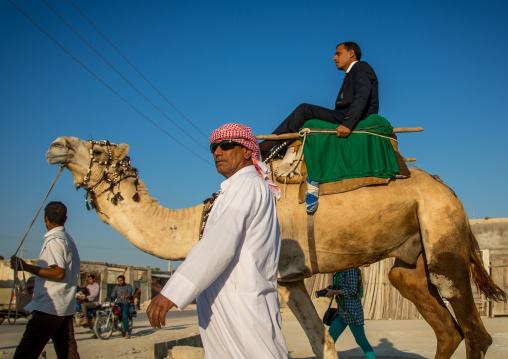 groom riding a camel during his wedding ceremony, Qeshm Island, Salakh, Iran