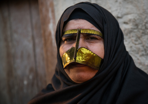 A bandari woman wearing a traditional gold mask called the burqa with a moustache shape, Qeshm island, Salakh, Iran