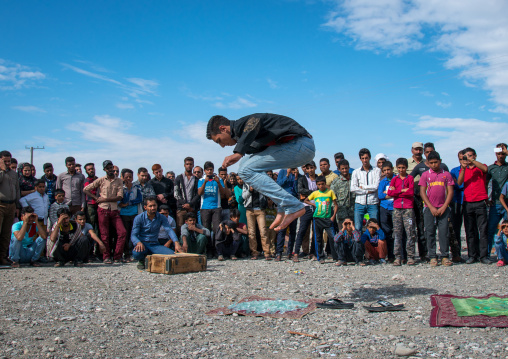 man jumping on broken glass during a show on a market, Hormozgan, Minab, Iran
