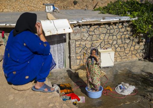 Women Washing Clothes In The Old Kurdish Village Of Palangan At Dusk, Iran