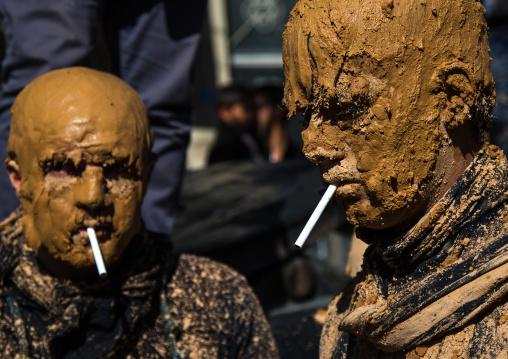 Iranian Shiite Muslim Men Covered In Mud Smoking Cigarettes During Ashura Day, Kurdistan Province, Bijar, Iran