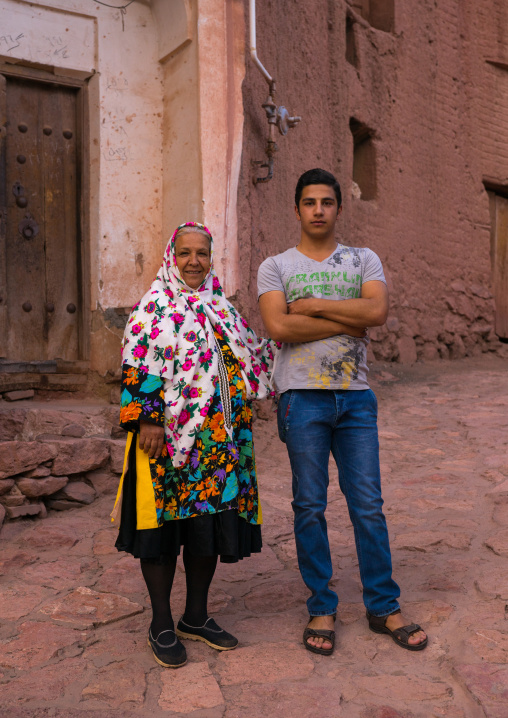 Portrait Of An Iranian Woman Wearing Traditional Floreal Chador With Her Son In Zoroastrian Village, Isfahan Province, Abyaneh, Iran