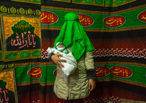 Iranian Woman With Green Veil Covering Her Face Holding A Baby Doll During Chehel Menbari Festival On Tasua To Commemorate Imam Hussein, Lorestan Province, Khorramabad, Iran
