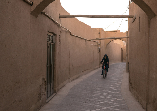 Girl Riding A Bicycle In A Narrow Street, Yazd Province, Yazd, Iran