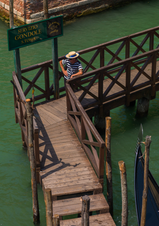 High angle view of a gondolier on a wooden pontoon, Veneto Region, Venice, Italy