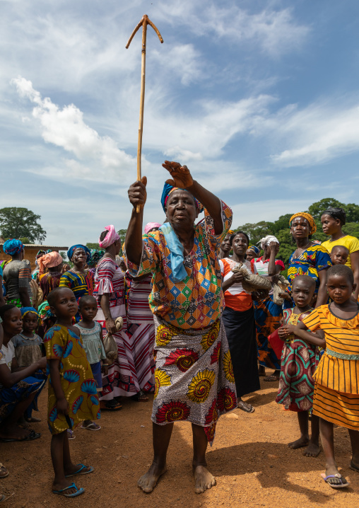 Dan tribe woman celebrating the yam harvest in a village and dancing with a wooden stick, Bafing, Godoufouma, Ivory Coast