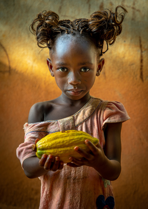 Cute african girl with a cocoa fruit pod in her hands, Région des Lacs, Yamoussoukro, Ivory Coast