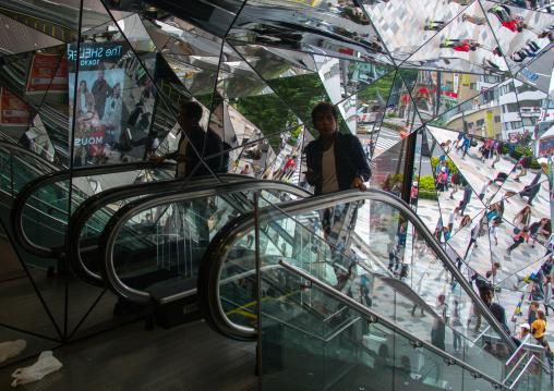 Walking people reflected on glass in tokyu plaza i, Kanto region, Tokyo, Japan