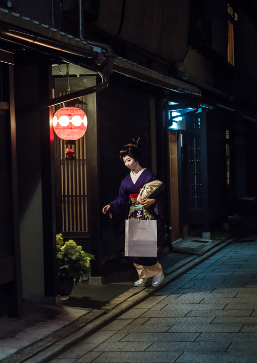 Geisha in the streets of gion going inside a house, Kansai region, Kyoto, Japan