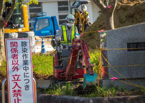 A sign warns people and workers remove top soil contaminated by nuclear radiations after the daiichi nuclear power plant explosion, Fukushima prefecture, Iitate, Japan
