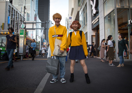 Young japanese woman and man shopping  in the street, Kanto region, Tokyo, Japan
