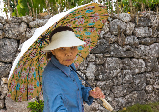 Senior japanese woman with an umbrella, Yaeyama Islands, Taketomi island, Japan
