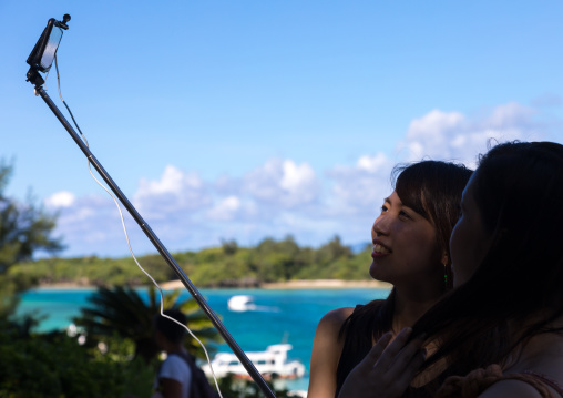 Japanese tourists taking selfie in Kabira bay, Yaeyama Islands, Ishigaki, Japan
