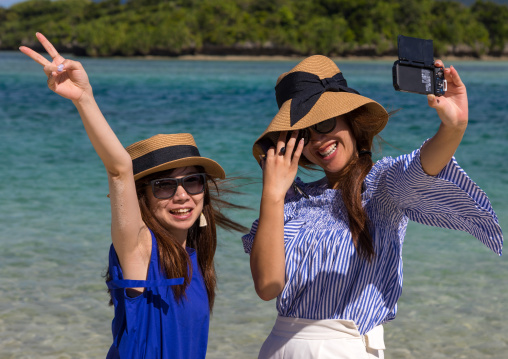 Japanese girls taking selfie in the tropical lagoon with clear blue water in Kabira bay, Yaeyama Islands, Ishigaki, Japan