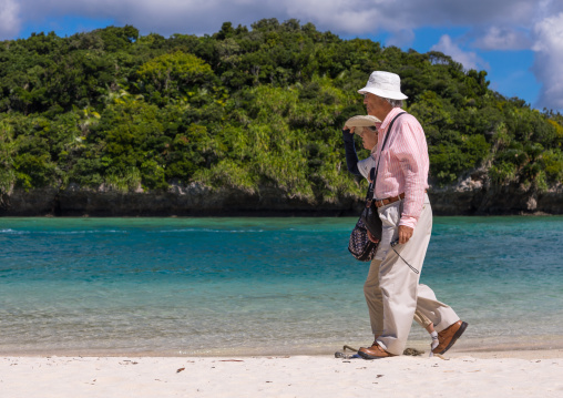 Old japanese couple walking along the tropical lagoon with clear blue water in Kabira bay, Yaeyama Islands, Ishigaki, Japan