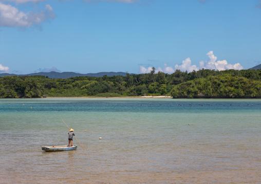 Japanese fisherman in tropical lagoon with clear blue water in Kabira bay, Yaeyama Islands, Ishigaki, Japan