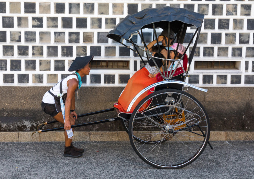 Rickshaw driver taking a picture of tourists in Bikan historical quarter, Okayama Prefecture, Kurashiki, Japan