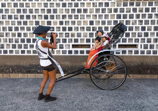 Rickshaw driver taking a picture of tourists in Bikan historical quarter, Okayama Prefecture, Kurashiki, Japan