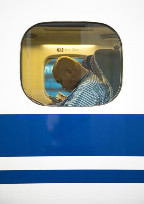 Passenger sleeping inside a Shinkansen train, Hypgo Prefecture, Himeji, Japan