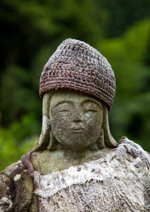 Peaceful stone religious statue with a hat, Izu peninsula, Izu, Japan