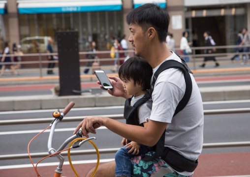 Father looking at his smart phone while riding a bicycle with his child, Kanto region, Tokyo, Japan