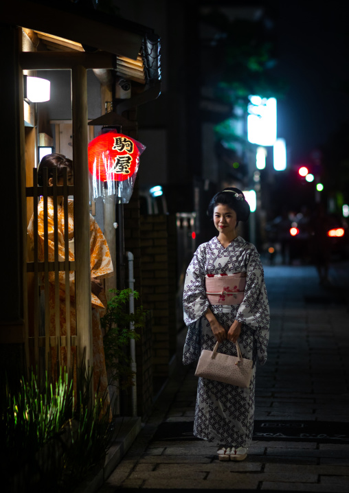 Portrait of a maiko called Chikasaya in front of her okiya, Kansai region, Kyoto, Japan