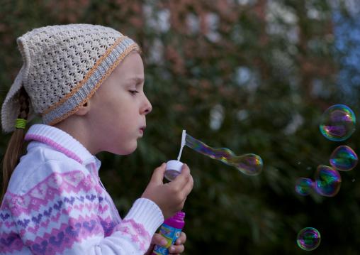 Alina, Ethnic Russian Girl Blowing Bubbles In Astana Park, Kazakhstan