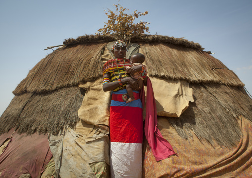 Rendille tribeswoman in front of her hut holding her baby, Marsabit district, Ngurunit, Kenya