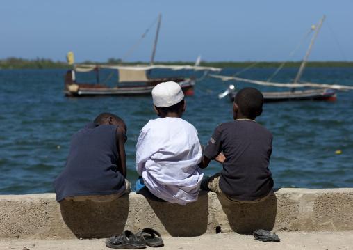 Three little muslim boys chatting alongside the dockside, Dhows in background, Lamu, Kenya