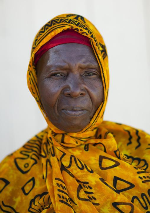 Mid adult woman wearing yellow veil portrait, Lamu, Kenya