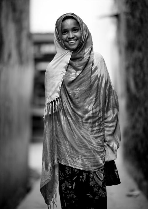 Teenage girl head and shoulders smiling at camera in street of lamu, Kenya