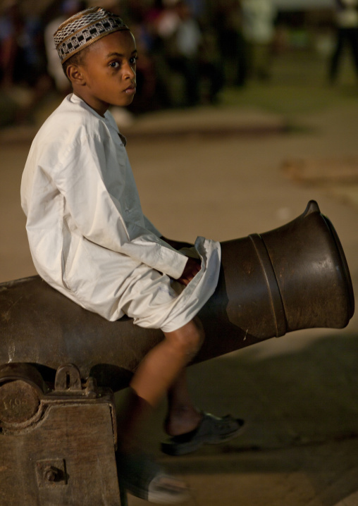 Concerned teenage boy with kofia, Sitting on a cannon