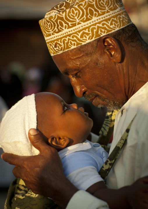Father carrying small baby  with coaled eyelids during maulidi, Lamu, Kenya
