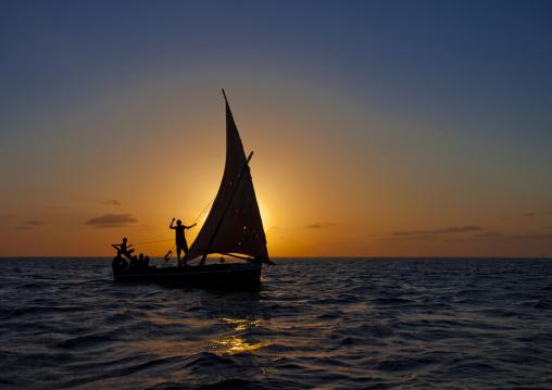 Two men waving hand, Sailing dhow boat at dusk, Lamu, Kenya