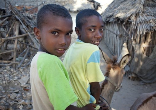 Two young boys riding one mule in the slums of lamu, Kenya