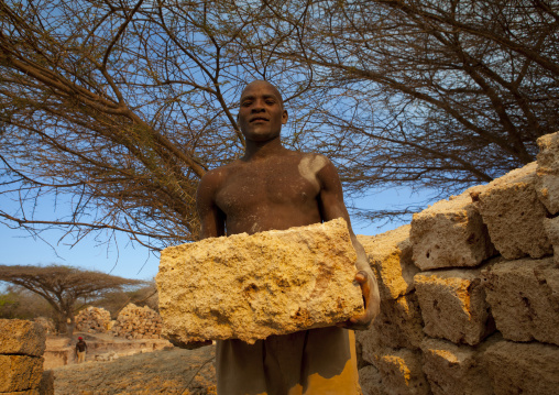 Worker holding yellow stone coral stone quarry, On manda island, Lamu, Kenya