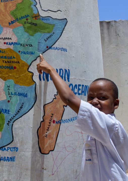 Young boy showing lamu on a painted map, Lamu school, Kenya