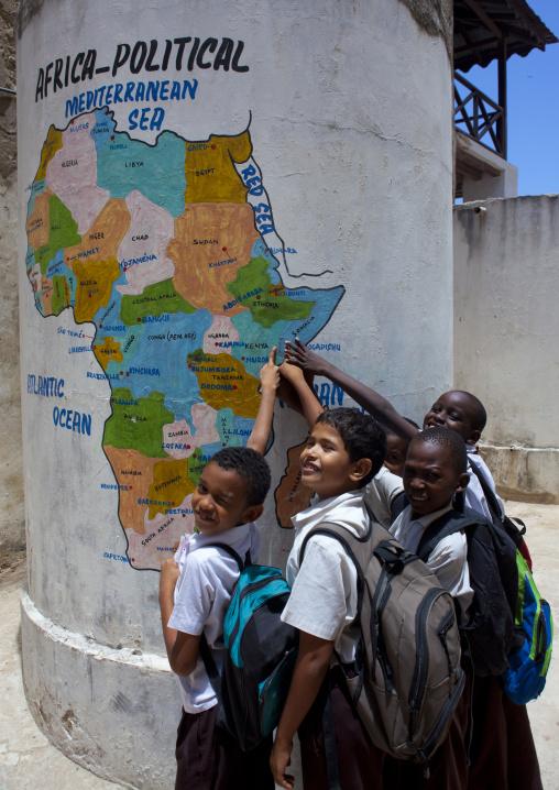 Group of male pupils showing lamu on painted map at school, Lamu, Kenya