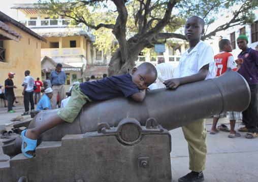 Little boy lazing on a cannon in  a street of lamu, Kenya