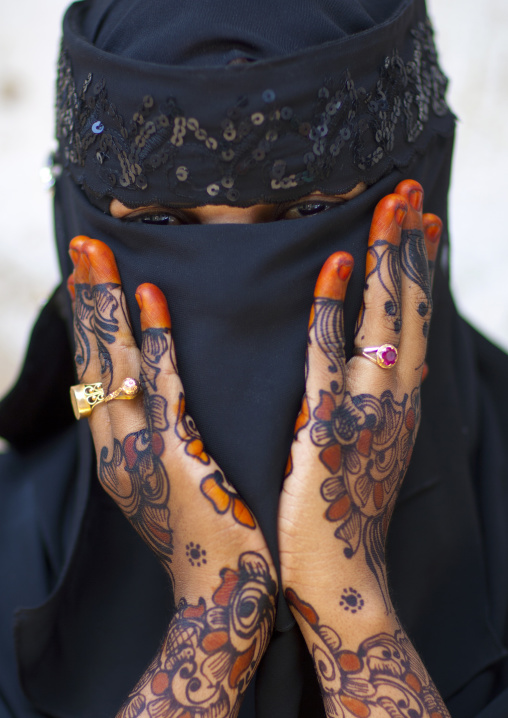 Unrecognizable young woman wearing hijab veil shows palm of her hand painted with henna and indigo blue, Lamu, Kenya