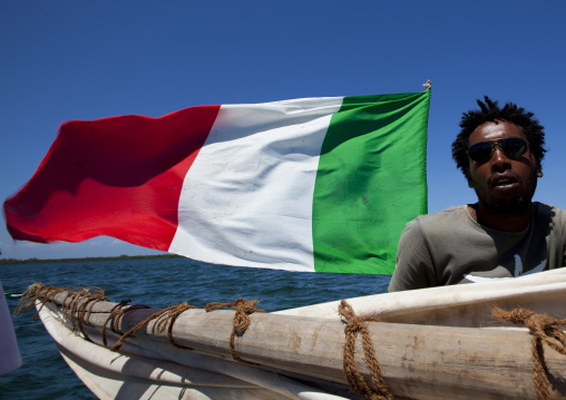 A man with italian flag and sunglasses on a dhow near lamu coast, Kenya