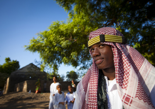 Muslim teenage boy wearing keffieh during the procession of the Maulid festival, Lamu County, Lamu, Kenya