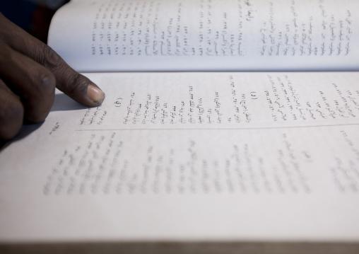 Forefinger of a witchdoctor reading jinn book, Lamu, Kenya