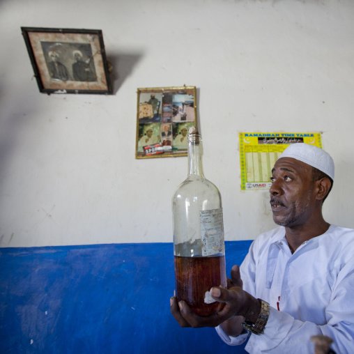Witch doctor holding a bottle of mysterious potion, Lamu, Kenya