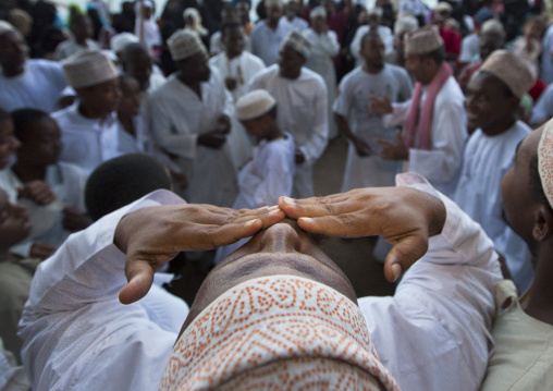 Man kissing blessing at the crow during maulidi festival celebration, Lamu, Kenya
