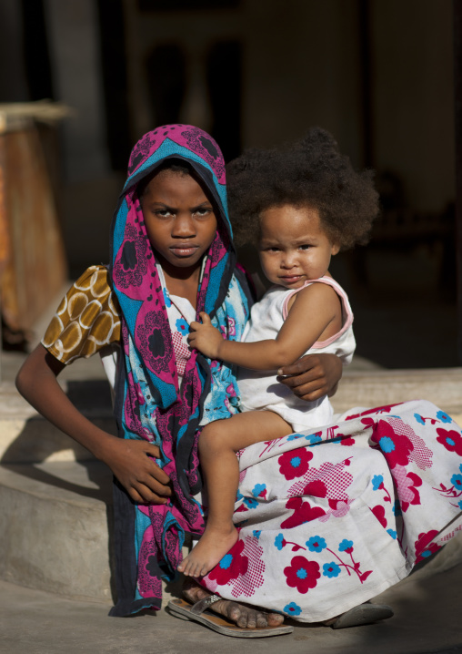 Worried teenage girl holding little baby in hands while seated on stair, Lamu, Kenya